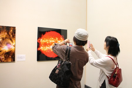 美術館で太陽の写真を撮る参加者.JPG